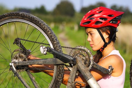 Bike repair. Woman repairing mountain bike. Stock Photo