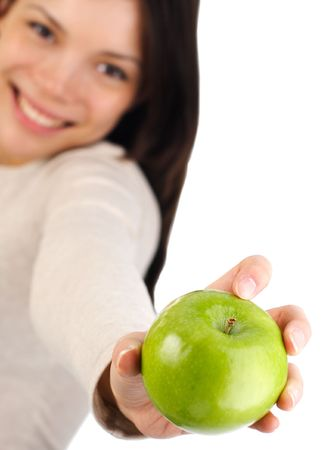 Eat healthy concept. Beautiful autumn woman giving you an apple. Isolated on white background. Shallow depth of field, focus on the apple Stock Photo - 5614662