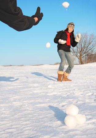 bolas de nieve: Snowball fight - la diversi�n de invierno. Pareja tirar bolas de nieve unos a otros. Foto de archivo