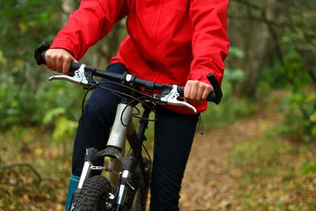mountainbike: Biking. Woman on mountainbike in autumn forest. Stock Photo