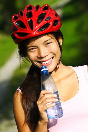 Excercise woman. Beautiful young woman enjoying a bottle of water outdoors during a bike trip photo