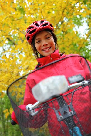 Woman biking in autumn forest. Strong colors. photo