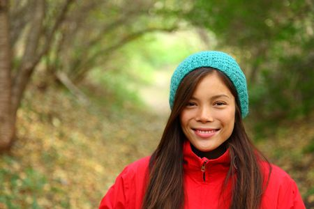 Autumn woman smiling. Beautiful woman walking in the forest on a fall day. photo