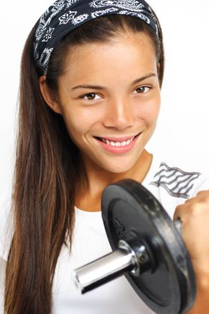 powe: Fitness woman. Attractive woman lifting weights and smiling at the camera. Closeup.