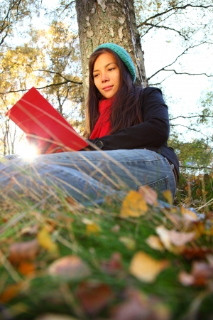 Reading outdoors in Autumn. Beautiful young woman reading a book outside in autumn. photo