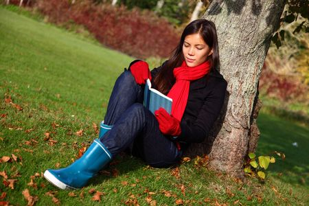 Woman reading book outdoors in park under tree in autumn. photo