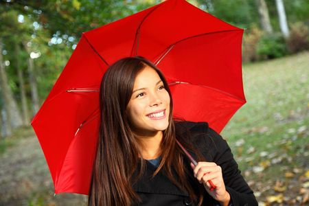 is raining: Red umbrella woman outdoors in autumn forest. Beautiful model.
