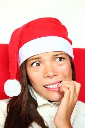Christmas woman with santa hat nervous biting nails. Beautiful mixed asian  caucasian model.  photo