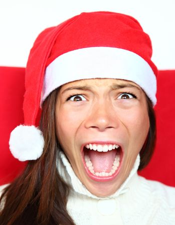 holiday stress: Screaming christmas woman with santa hat. Beautiful mixed asian  caucasian model.