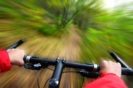 mountainbike: Speed on Mountainbike. Biking in the forest motion blurred for speed effect