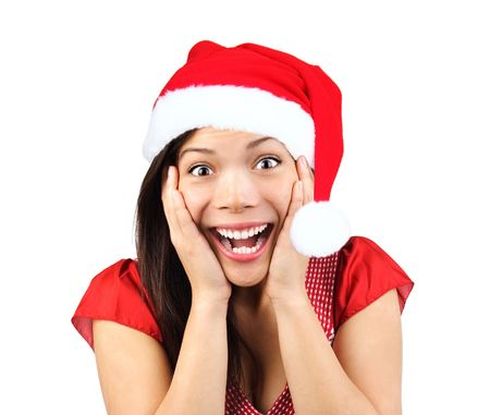 Christmas girl very excited and surprised holding her head. Beautiful mixed asian / caucasian model. Isolated on seamless white background. Stock Photo - 5775022
