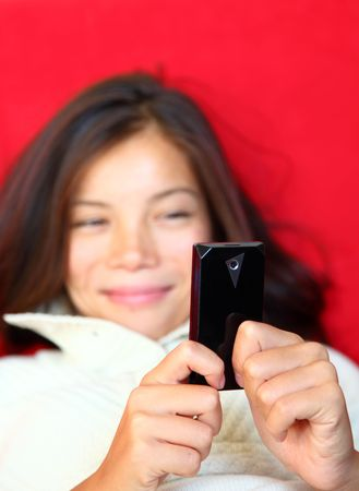 SMS on cellphone. Beautiful woman smiling being happy reading a sms on her mobile phone. Mixed race asian  caucasian model. Shallow depth of field, focus on phone. photo
