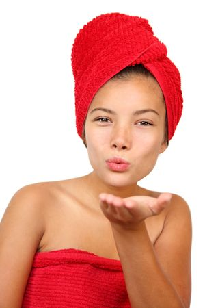 Woman blowing a finger kiss at the camera. Just out of the shower holding towel. Beautiful young mixed race asian  caucasian woman model.  photo