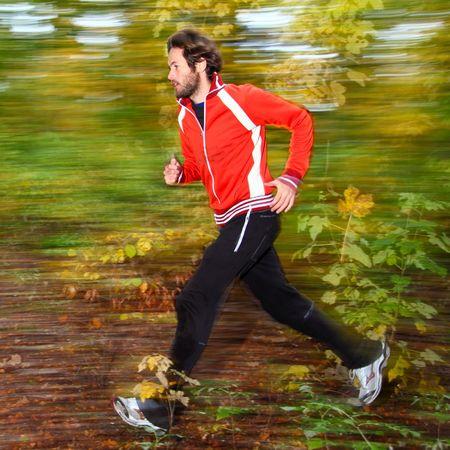 autum: Man running in autum forest. Stock Photo