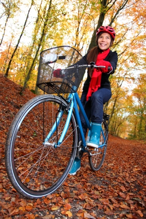 Biking, Woman on bike in autumn forest. Beautiful mixed asian  caucasian model. photo