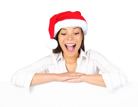 Christmas billbord sign woman. Beautiful mixed asian  caucasian woman leaning over blank billboard sign looking down being excited and surprised. Isolated on white background. photo