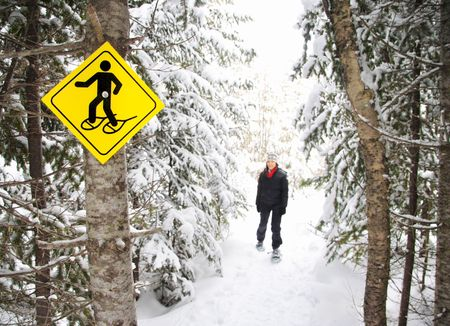 snowshoeing: Snowshoes. Young woman snowshoeing in pine forest near Baie Saint-Paul, Quebec, Canada.
