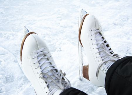winterday: Ice skates. Closeup of classical figure skating ice skates on ice outdoors on lake in Quebec, Canada