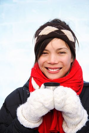 Woman drinking hot coffee or tea outdoors in winter. Mixed ethnic asian  caucasian model. The background is an ice wall. photo
