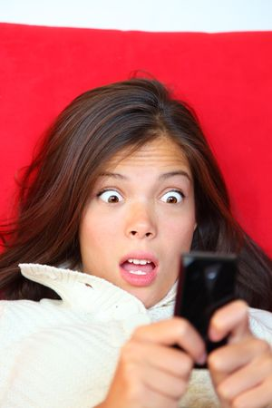 sms text: Surprised woman reading shocking sms text message.
