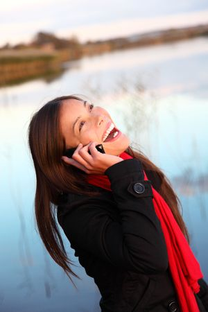 Laughing woman on the phone. Casual and natural outside by the water.  photo