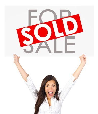 property owners: Young successful mixed race asian  caucasian real estate agent or owner holding a for sale sign for a sold house. Isolated on white background.