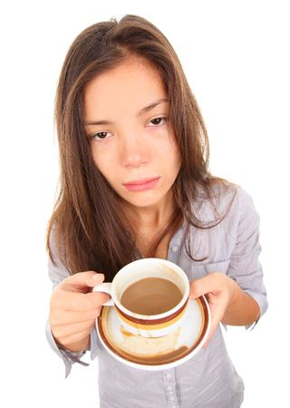 waking: Tired woman with empty and bored eyes looking at the camera having spilled a little coffee. Beautiful mixed race asian  caucasian model isolated on white background. Stock Photo