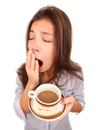 agotado: Mujer cansada bostezo derram� un poco de caf�. Hermosa raza mixta modelo asi�tico  cauc�sicos aislado sobre fondo blanco.