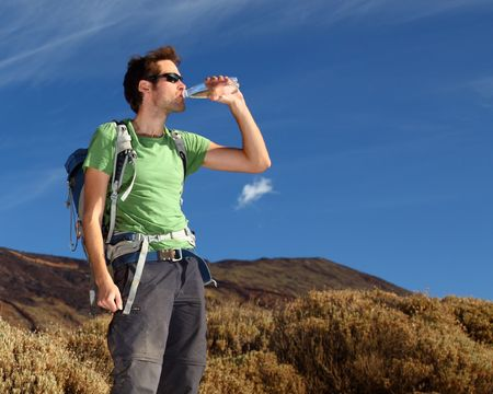 trekking pole: Man hiking. Young man hiking  backpacking in very scenic and beautiful volcanic landscape on the volcano, Teide, Tenerife, Spain.  Stock Photo