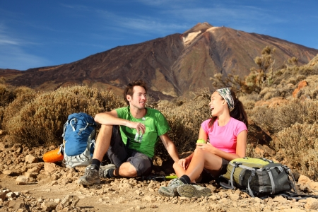 People hiking. Young beautiful couple taking a break, relaxing and eating during a hike  backpacking trip in the beautiful and wild volcanic landscape in the national park on the volcano, Teide, Tenerife, Spain.  photo