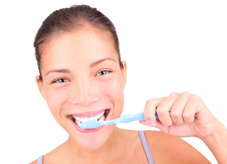toothbrushing: Brushing teeth. Closeup of woman actually brushing her teeth with toothpaste and a manual toothbrush. Beautiful mixed race asian  caucasian model.