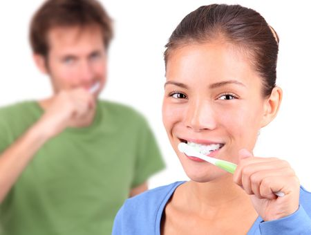 Young mixed race couple brushing teeth together on white background. photo