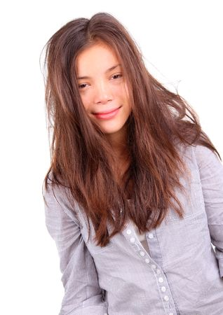Morning Hair. Tired woman with very messy long morning hair and a silly smile - just out of bed. Beautiful mixed asian  caucasian model isolated on white background. photo