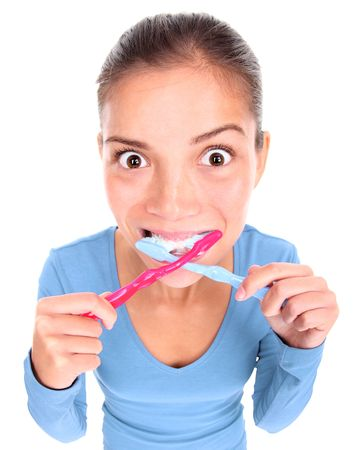 toothbrushing: Funny woman with two toothbrushes brushing teeth. Isolated on white background. Concepts could be: 1) Being too busy and stressed in the morning and desperate to win some time. 2) Being obsessed with personal hygiene. 3) ?