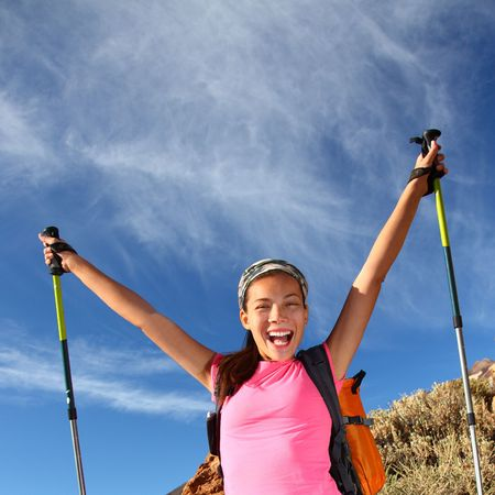 walking pole: Happy woman hiker holding her arms in the air in a feeling of success having reached the summit. From a hike  backpacking trip in the beautiful  volcanic landscape on the volcano, Teide, Tenerife. Stock Photo