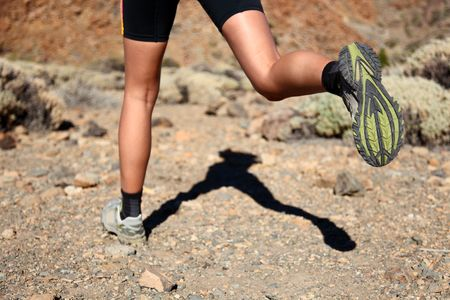 Woman running on trail. Closeup of woman trail running in desert on the volcano Teide, Tenerife.  photo