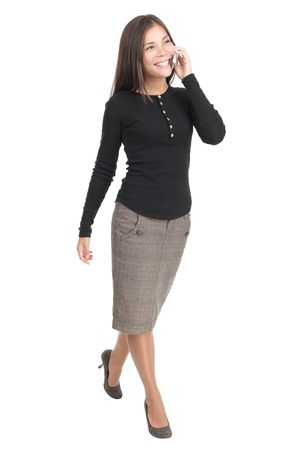 secretary phone: Businesswoman isolated walking in full length with mobile phone. Casual beautiful young mixed race chinese  caucasian business woman isolated on seamless white background.