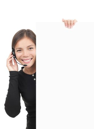 Call center woman with headset holding blank white billboard sign. Smiling and freindly young mixed race chinese  caucasian secretary or telemarketing assistant isolated on white background. photo
