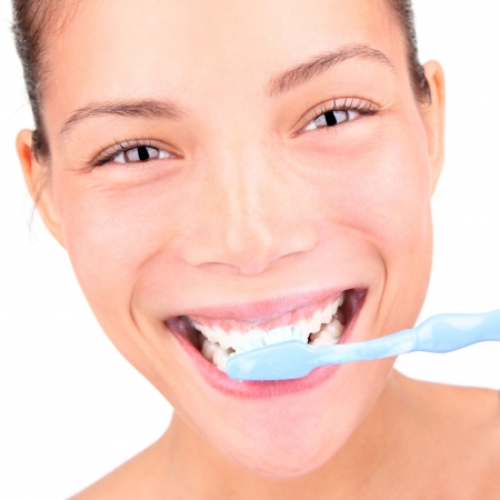 toothbrushing: Brushing teeth. Closeup of woman brushing her teeth with toothpaste and a manual toothbrush. Beautiful mixed race asian  caucasian model. Stock Photo