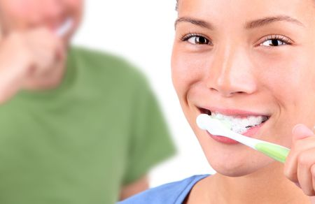 toothbrushing: Young couple brushing teeth together on white background. Stock Photo