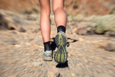 trail running: Woman running on trail. Zoom motion blurred closeup of woman trail running in desert on the volcano Teide, Tenerife.