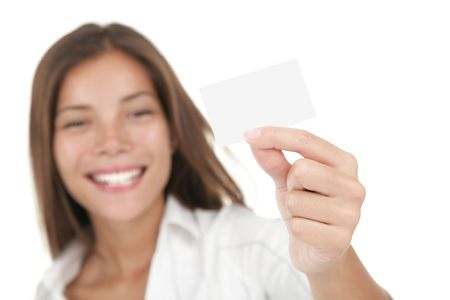 Business card. Casual young and attractive businesswoman showing her blank white business card / empty sign. Mixed race chinese / caucasian model isolated on seamless white background. Stock Photo - 6179533