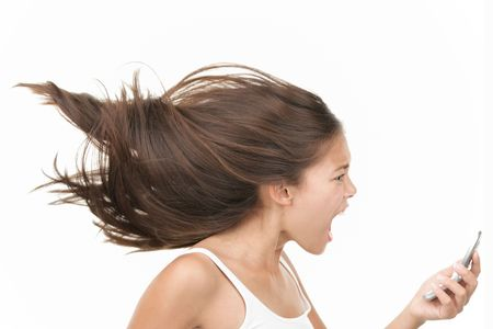 Screaming angry woman on the mobile phone. Dynamic and energetic image of young mixed race chinese  caucasian woman isolated on seamless white background.  photo