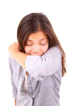 viral: Woman having the flu and sneezing on her sleeve in the crook of her arm. Isolated on white background.