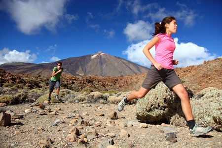 trail running: Couple trail running in spectacular volcano landscape on Teide, Tenerife.  Stock Photo