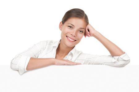 Femme de signe de bannière. Femme debout derrière et penchement sur un espace blanc billboard / placard. Belle course mixte chinois / caucasien modèle. Isolé sur fond blanc.