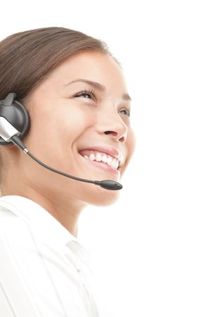 Headset woman in semi profile - smiling very kindly. Closeup of beautiful young mixed race chinese / caucasian secretary / assistant speaking with headphones while working in call center. Isolated on seamless white background. Stock Photo - 6186248
