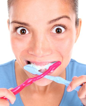 toothbrushing: Funny woman with two toothbrushes brushing teeth. Isolated on white background. Concepts could be: 1) Being too busy and stressed in the morning and desperate to win some time. 2) crazy and obsessed with personal hygiene...