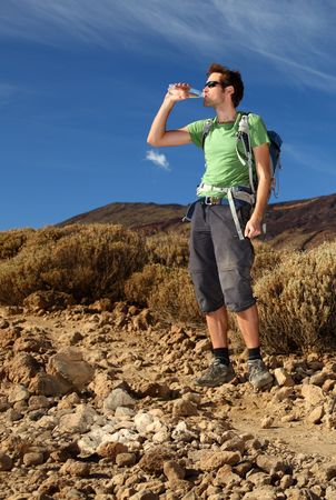 Hiker. Young man hiking  backpacking in very scenic and beautiful volcanic landscape on the volcano, Teide, Tenerife.  photo