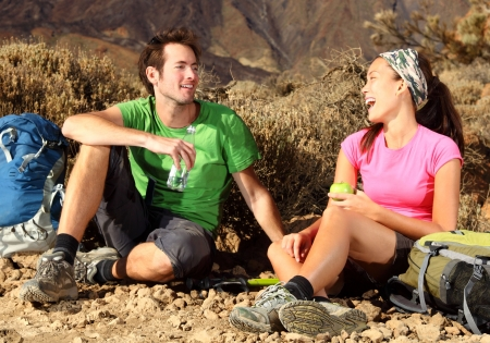 backpacking: Couple having fun. Couple laughing during a break from hiking on a backpacking trip in the beautiful volcanic landscape. Location: The national park on the volcano, Teide, Tenerife, Spain.  Stock Photo